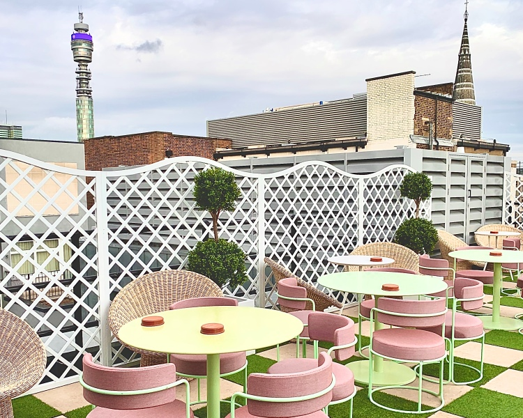 BT Tower in the back ground with empty pink chairs in front on the rooftop club The Wing